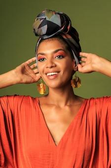 Modello di moda giovane con stile africano tradizionale con sciarpa, orecchini e trucco