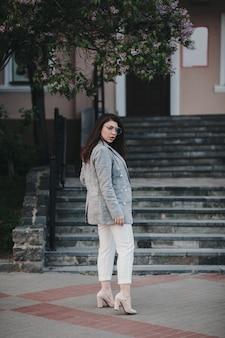 Bruna della donna di moda giovane in vestito elegante che cammina sulla strada della città