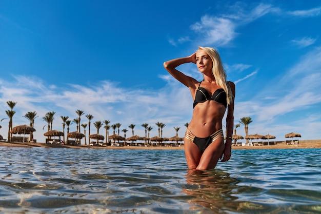 Moda giovane donna in piedi in acqua sulla spiaggia.