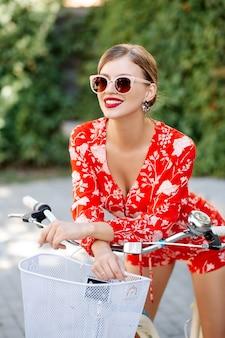 Giovane bella ragazza sexy alla moda in un vestito rosso in estate in una città che indossa occhiali da sole in sella a una bicicletta