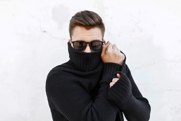Giovane ragazzo alla moda in occhiali da sole neri