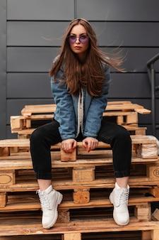 Giovane donna hipster alla moda in abiti giovanili casual alla moda in eleganti occhiali viola posa all'aperto in città. la modella europea sexy ragazza affascinante si siede su pallet di legno in strada.