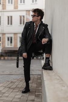 Giovane uomo alla moda hipster in eleganti vestiti neri oversize in occhiali da sole che riposano con una sigaretta vicino a un edificio vintage sulla strada. bel ragazzo brutale in gioventù alla moda indossare fuma all'aperto.