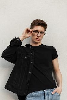 Il giovane uomo alla moda raddrizza gli occhiali alla moda vicino al muro vintage in strada. bel ragazzo modello in giacca di jeans nera giovanile in blue jeans in t-shirt alla moda vicino all'edificio in città.