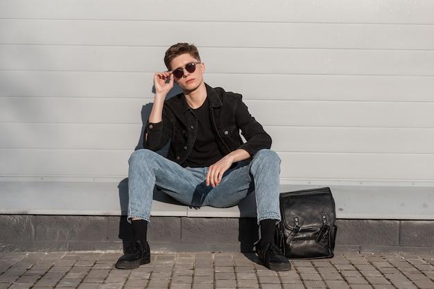 Il giovane uomo alla moda raddrizza gli occhiali da sole alla moda vicino alla parete dell'annata il giorno soleggiato luminoso