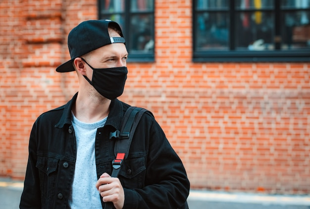 La maschera nera protettiva di abbigliamento casual della gioventù dell'uomo alla moda giovane cammina attraverso il tramonto urbano della città.