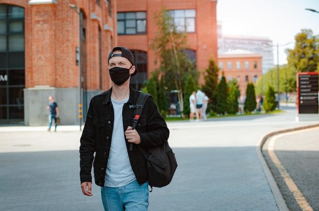 La maschera nera protettiva di abbigliamento casual della gioventù dell'uomo alla moda giovane cammina attraverso la città urbana