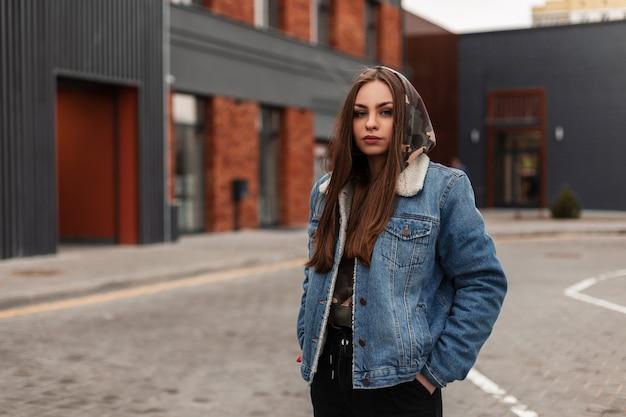 La giovane donna abbastanza urbana alla moda in giacca di jeans blu giovanile è in posa vicino all'edificio in città. la bella ragazza americana in jeans alla moda indossa per strada. abiti di moda casual per le donne.