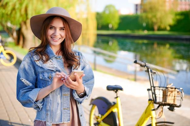 Giovane donna alla moda in cappello e giacca di jeans utilizza lo smartphone nel parco pubblico della città davanti alla bici gialla a noleggio