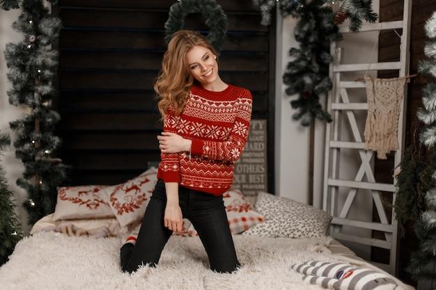 Giovane donna alla moda in un elegante maglione vintage in posa su un letto