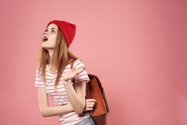 Giovane donna alla moda che indossa occhiali da sole ahah abiti casual in posa sfondo rosa