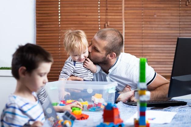 Il giovane genitore dell'uomo di affari del padre interrompe dai suoi figli dei bambini mentre lavora nella casa. lavoro online e educazione dei figli allo stesso tempo.