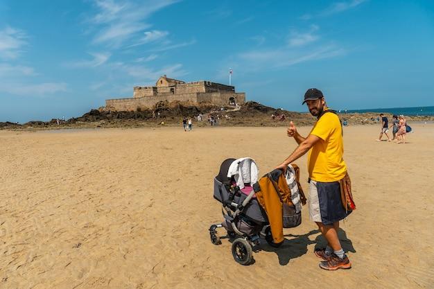 Un giovane padre che si gode l'estate sulla grande plage du sillon de saint-malo nella bretagna francese, france
