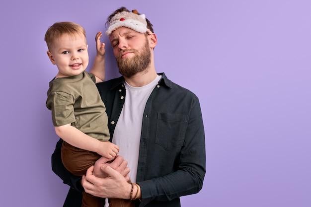 Giovane padre in maschera per gli occhi per dormire, stare in piedi tenendo in mano il ragazzino, vuole dormire la mattina prima della giornata lavorativa.