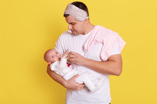 Giovane padre che alimenta il suo bambino mentre posa isolata sopra la parete gialla