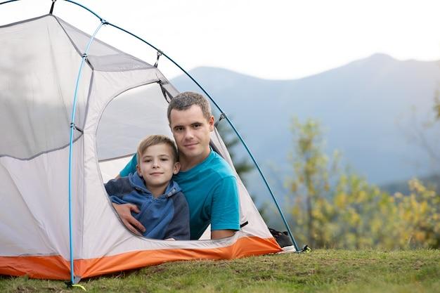 Il giovane padre e il figlio di suo figlio fanno un'escursione insieme in montagna d'estate. famiglia attiva che riposa in tenda turistica.