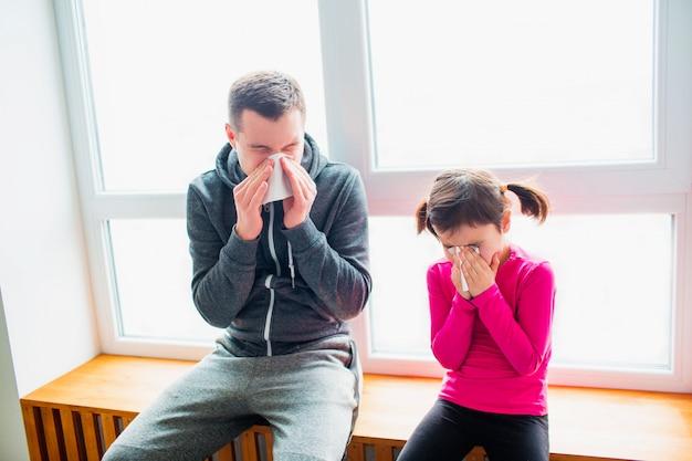 Il giovane padre e la sua piccola figlia carina hanno fazzoletto e naso che cola dopo l'allenamento su una stuoia al coperto. carino bambino e papà hanno esercizi vicino alla finestra nella sua stanza.