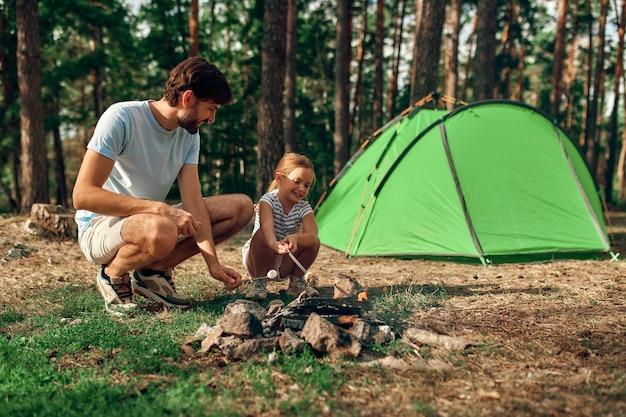Un giovane padre e sua figlia siedono accanto a un falò vicino a una tenda e grigliano marshmallow durante il fine settimana in una foresta di pini. campeggio, ricreazione, escursionismo.