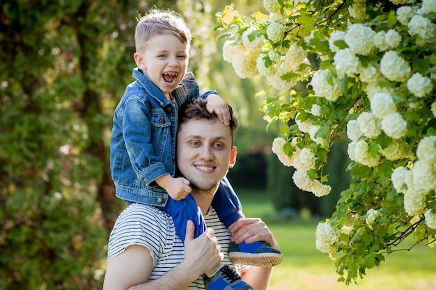 Giovane padre e suo figlio sorridente nel parco, abbracciando e godendo del tempo insieme, celebrazione della festa del papà.