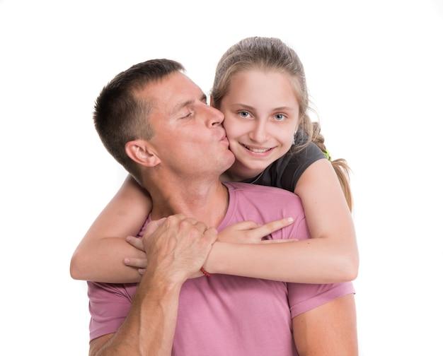 Giovane padre che bacia figlia sorridente su un muro bianco