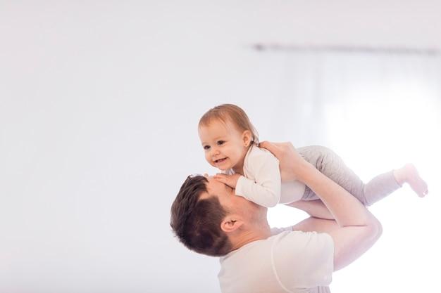 Il giovane padre solleva la sua piccola bambina, dentro la stanza