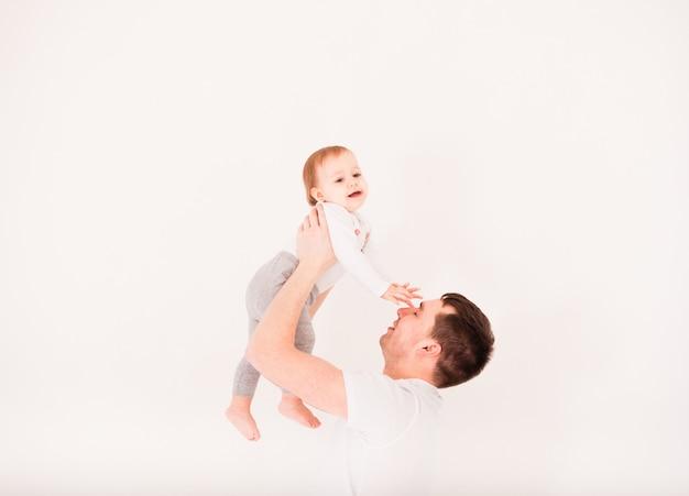 Il giovane padre solleva la sua piccola bambina, isolata su bianco