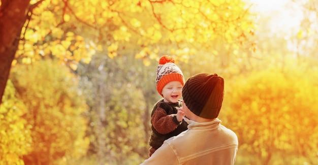 Giovane padre e figlio piccolo nella sosta di autunno