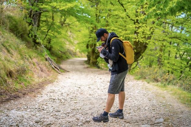 Un giovane padre che ripone bene il neonato nello zaino su un sentiero nella foresta che si dirige al picnic con la famiglia