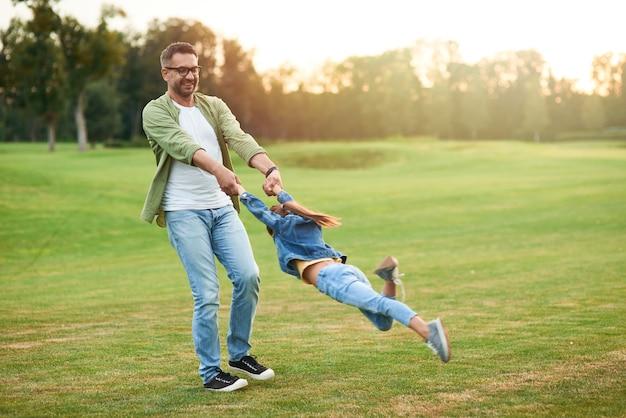 Giovane padre che gioca e si diverte con la sua piccola figlia nel bellissimo parco verde su a