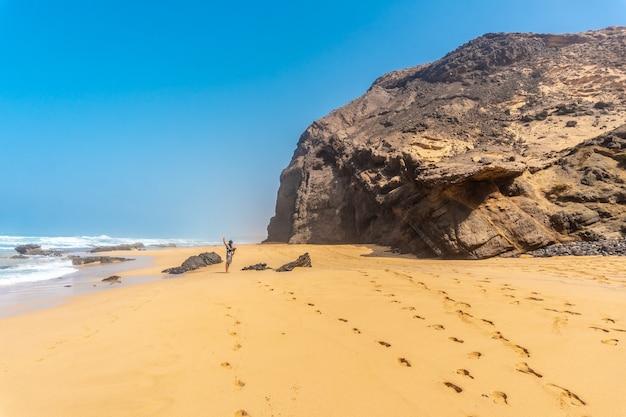 Un giovane padre nel roque del moro della spiaggia di cofete del parco naturale di jandia, barlovento, a sud di fuerteventura, isole canarie. spagna