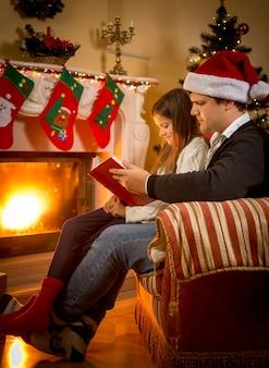 Giovane padre seduto con la figlia al caminetto e raccontando una storia alla vigilia di natale