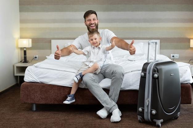 Un giovane padre e figlio si siedono su un letto in un hotel con una valigia e ridono.