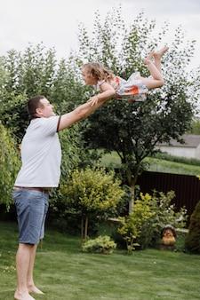 Giovane padre che getta la sua bambina in alto nel cielo nel parco in una giornata estiva