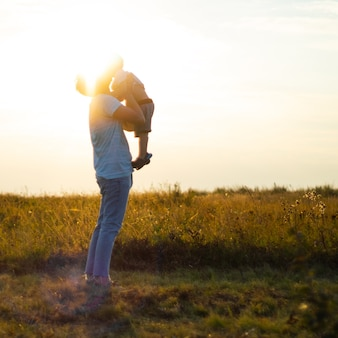 Il giovane padre vomita il suo figlio carino e piccolo all'aria aperta. festa del papà, padre e figlio di suo figlio che giocano e abbracciano all'aperto.