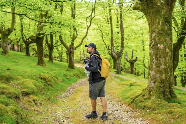 Un giovane padre che cammina con il neonato nello zaino su un sentiero nel bosco diretto al picnic con la famiglia