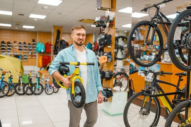 Giovane padre con bicicletta per bambini, shopping nel negozio di articoli sportivi.