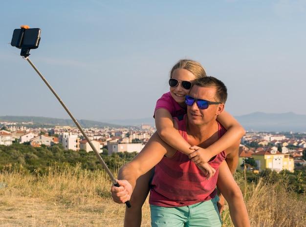 Giovane padre con la figlia che prende selfie all'aperto