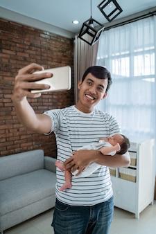 Giovane padre con la figlia che prende selfie