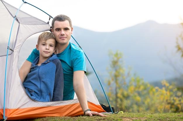 Giovane padre con suo figlio figlio che riposa insieme in una tenda da escursionista in montagna d'estate
