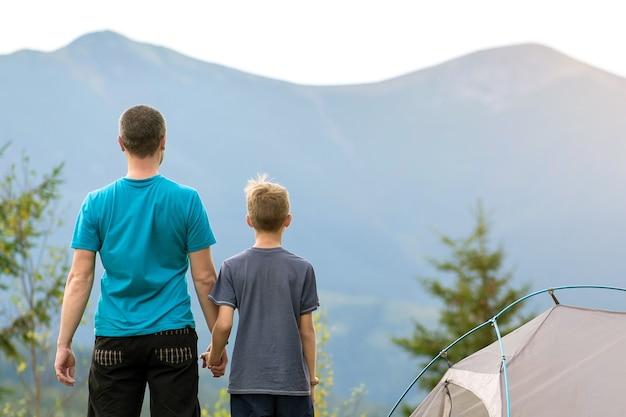 Giovane padre con suo figlio figlio in piedi insieme vicino a una tenda da escursionista in montagna estiva.