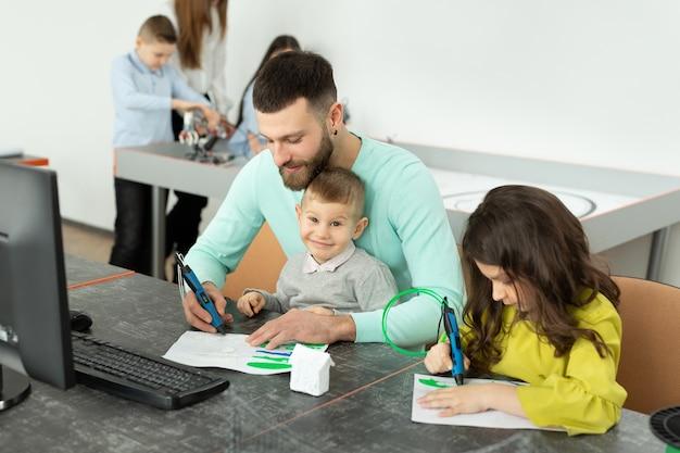Il giovane padre con suo figlio e sua figlia disegnano un disegno usando una penna 3d durante le lezioni di robotica