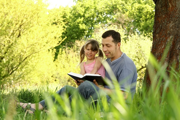 Giovane padre con una figlia piccola che legge la bibbia