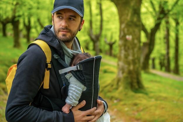 Un giovane padre con uno zaino giallo e un berretto nero che cammina con il neonato nello zaino su un sentiero nel bosco