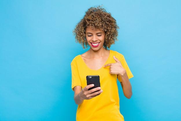 Young si sente felice, sorpreso e orgoglioso, indicando se stesso con uno sguardo eccitato e stupito con un telefono cellulare