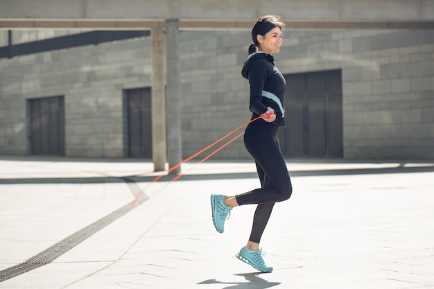 Giovane donna esercizio attivo allenamento sulla strada fuori saltando