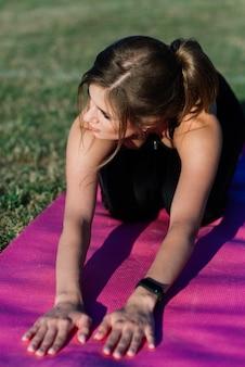 Giovane donna sola allo stadio che fa yoga