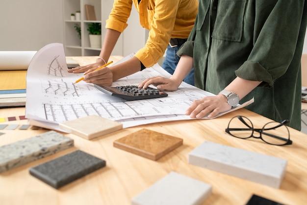 Giovane architetto femminile che punta al progetto srotolato e spiega lo schizzo al suo collega che effettua i calcoli vicino alla riunione di lavoro
