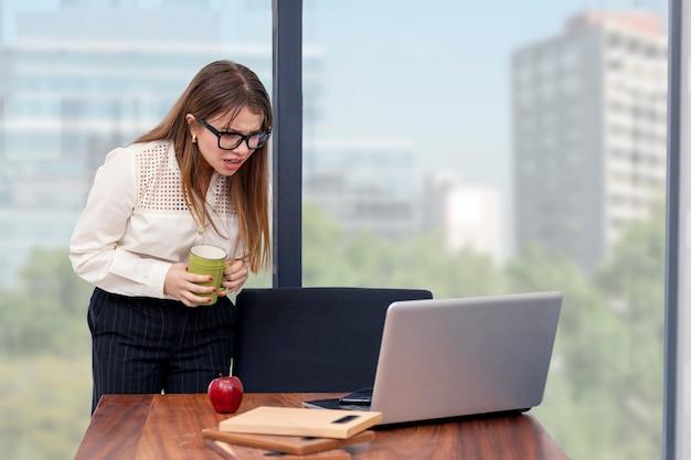 Giovane architetto donna con un caffè in mano che lavora da casa guardando il suo computer con