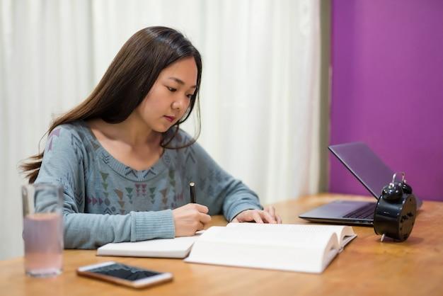 La giovane studentessa asiatica in casa legge il libro di testo e prende nota del libro, del tavolo di lavoro e del computer portatile, concetto di affari. lezione seria della ragazza asiatica per l'esame finale.