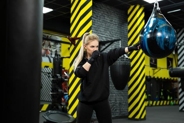 Giovane atleta femminile in guantoni da boxe blu colpisce una pera sul ring.